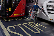 An urban cyclist leans against a tour coach in central London.