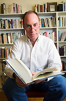 A portrait of an early 50's man wearing reading glasses and holding a large book in front of some book cases...Model Release: 20070111_MR_A.Property Release: 20070111_PR_A