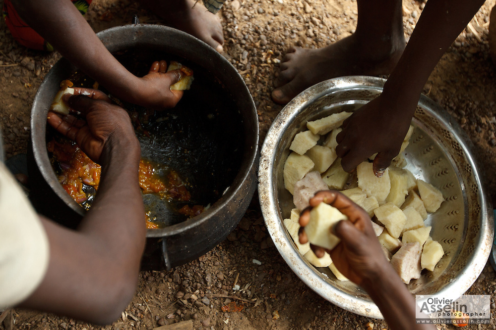 A group of boys share a meal of boiled yams and vegetable sauce on a cocoa plantation near the town of Moussadougou, Bas-Sassandra region, Cote d'Ivoire on Monday March 5, 2012.