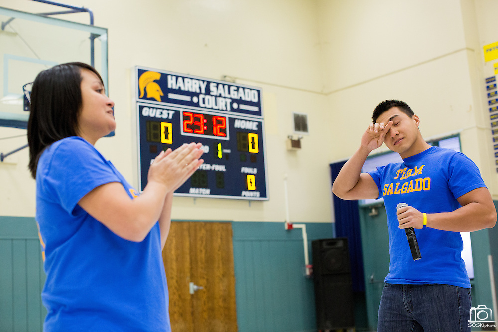 Siblings Teresa Salgado-Ellis and Jeremy Salgado wipe away tears as they make a statement about their father, Harry Salgado, during the Harry Salgado scoreboard dedication ceremony at Sierramont Middle School in San Jose, California, on January 8, 2015. (Stan Olszewski/SOSKIphoto)