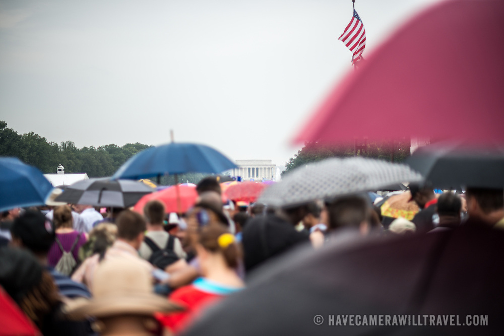 "People shield themselves from the light rain with umbrellas on Washington DC's National Mall at the commemoration of the 50th anniversary of the 1963 March on Washington famously remembered for civil right leader Martin Luther King Jr's ""I Have a Dream"" speech."