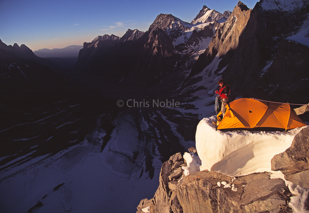 "The late American mountaineer Alex Lowe coils a rope at a camp while climbing ""The Bird"" a peak in the Ak Su Region of the Pamir Atlai Mountains, Kyrgyzstan."