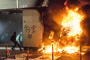 HONG KONG: Sunday 20 October 2019 A masked anti-government protester throws boxes to fuel the fire at the entrance to Chinese mobile phone store Xiaomi as it burns on Sunday in Hong Kong. Hundreds of thousands of protesters marched through the city's streets in defiance of the march being denied permission to take place as demonstrations roll into a 14th week. <br /> Rick Findler / Story Picture Agency