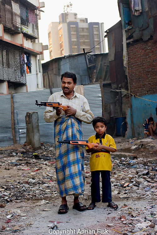 In Dharavi, the slum made famous by the film 'Slumdog millianire', a father stands with son in the early morn - 2007