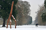 © Licensed to London News Pictures. 19/01/2013. Kew, UK A coupe walk past a sculpture by artist David Nash. People enjoy the snow at Kew Gardens in West London today 19th January 2013. More cold weather and snow are expected over the coming days.  Photo credit : Stephen Simpson/LNP