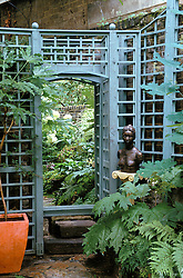 Shady corner with large mirror framed by blue painted trellis. Sculpture on plinth by Camilla Shivarg.