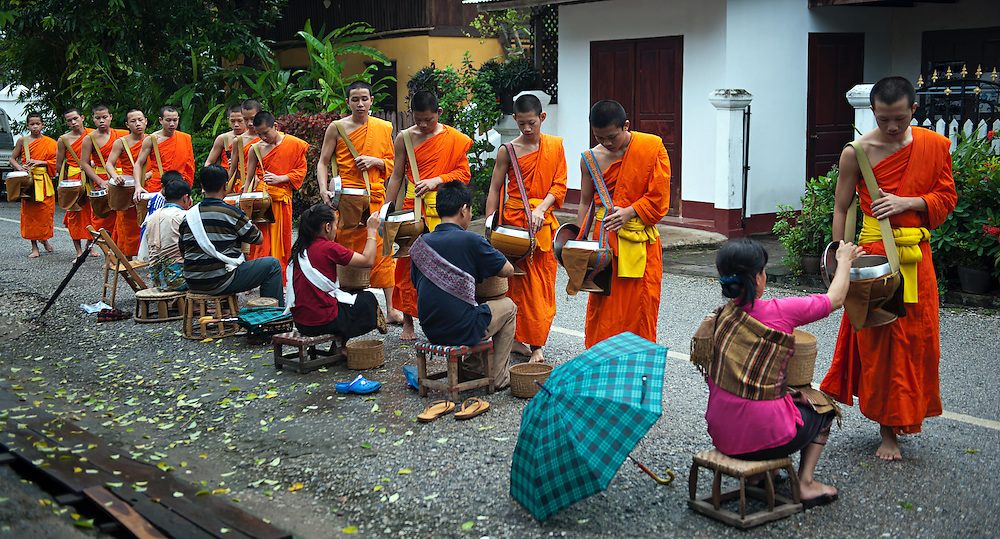 Novices and monks collecting alms in Luang Prabang, Laos.