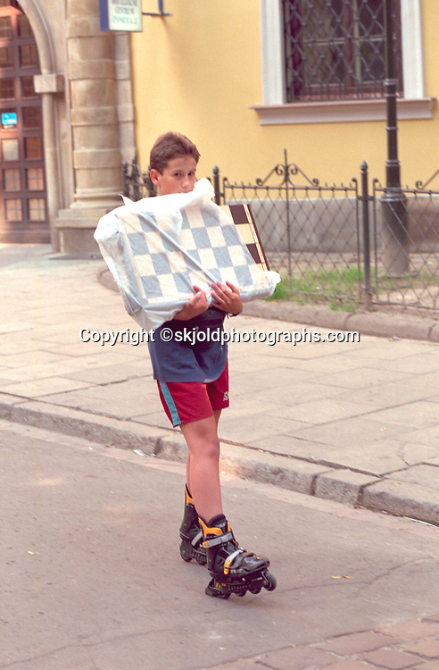Boy age 15 rollerblading home with new chess set.  Krakow Poland