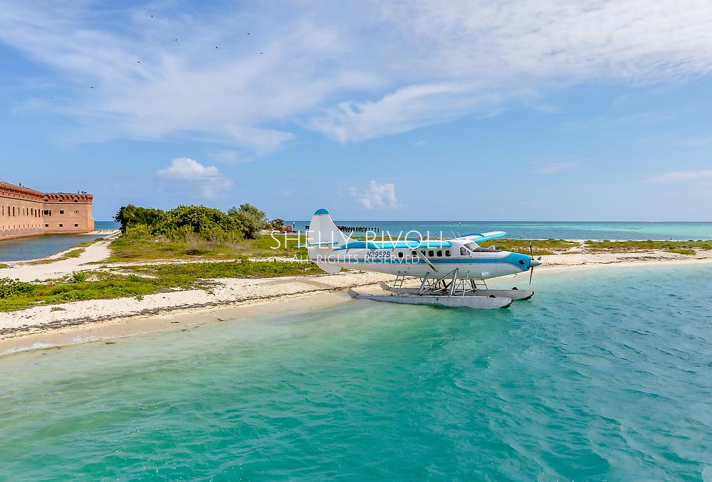 A seaplane at Dry Tortugas National Park awaits on turquoise water by a white sand beach. Historic Fort Jefferson is seen in the background.