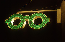 Illuminated neon sign outside opticians in form of a pair of spectacles,