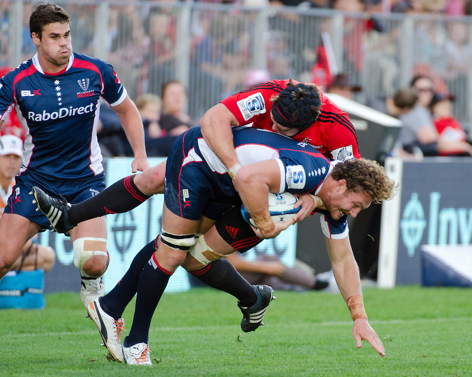 Rebels Scott Higginbotham, centre, attempts to break through the tackle of  Crusaders Matt Todd in the Super Rugby match at AMI Stadium in Christchurch, New Zealand, Sunday, April 28, 2013. Credit:SNPA / David Alexander.