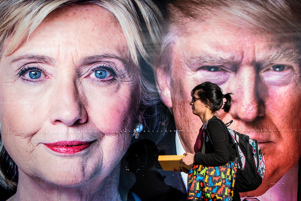 People walks past two portraits of the presidential candidates, pasted on a CNN Airstream trailer outside the debate area. The Democrate and Republican nominees for US President, Hillary Rodham Clinton and Donald John Trump, met on Sep. 26th for the first head to head Presidential Debate at the Hofstra University in Long Island.