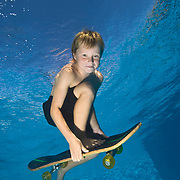 8 year old boy pretending to skate board underwater in swimming pool  MR