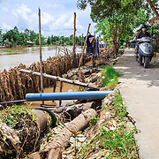 CAPTION: A section of the erosion barrier, which has recently been completed. Flooding and excessive boat traffic have both been the cause of erosion, damaging roads and houses that run alongside the river. Local communities are in the process of building erosion barriers several metres from the riverbank. LOCATION: An Binh Ward, Can Tho, Vietnam. INDIVIDUAL(S) PHOTOGRAPHED: N/A.