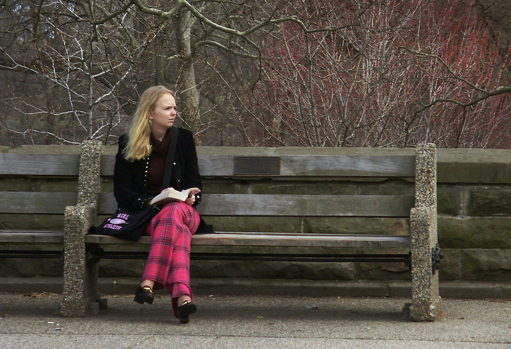 Woman on a park bench on a cold, very early Spring day.