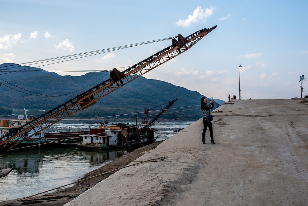 A tourist takes a selfie near a fleet of sand dredging vessels in Simaogangzhen, Yunan, China. The dredged sand is sold locally and to large scale construction sites in nearby major cities such as Kunming and Jinhong.