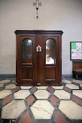 person sitting in a confessional Italy