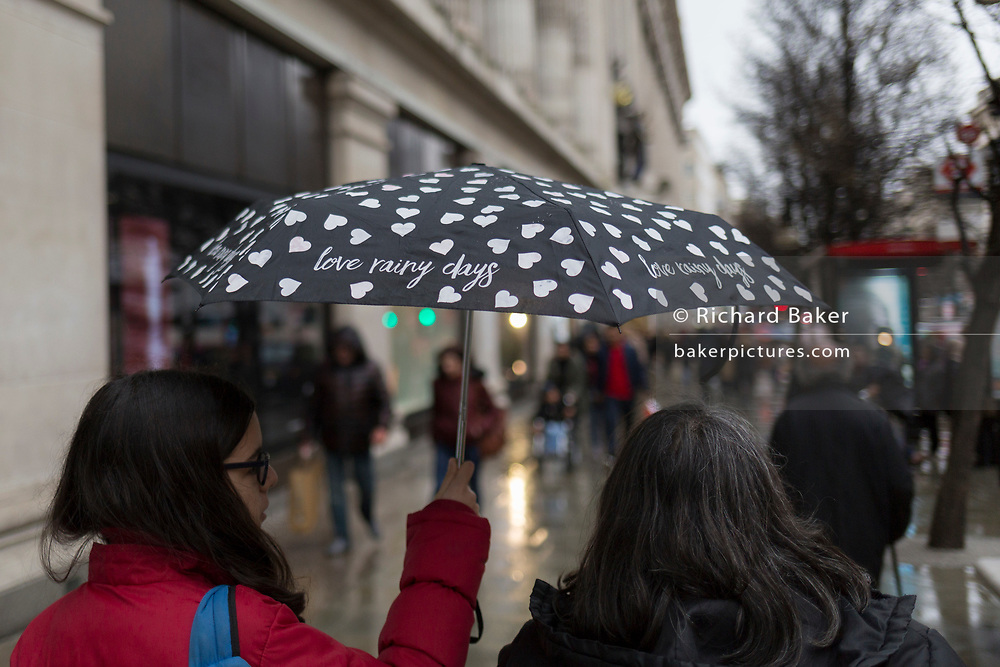 Shoppers carry an umbrella with the words 'love rainy days' outside the Selfridge's department store on Oxford Street, on 4th March 2019, in London England.