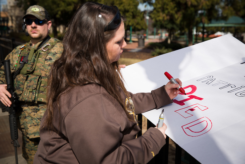 The Georgia Security Force III% militia holds a protest on Marietta Street in downtown Atlanta on Saturday, Feb. 6, 2016. The protest was partly inspired by the death of LaVoy Finicum by federal authorities. Here, Stacey Harris makes a sign for the protest. Photo by Kevin D. Liles/kevindliles.com