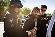 30 NOVEMBER 2011 - PHOENIX, AZ:    Phoenix police arrest anti-ALEC protesters at the Westin Kierland Resort and Spa Wednesday. Police pepper sprayed the crowd several times and arrested six or seven people during the melee. About 300 people picketed the American Legislative Exchange Council (ALEC) conference at the Westin Kierland Resort and Spa in Phoenix, AZ, Wednesday. The protesters claim ALEC, a conservative think tank, violates its tax exempt status by engaging in lobbying, a charge ALEC officials deny. Many conservative pieces of legislation, like Arizona's anti-immigration bill SB1070, originate with ALEC conferences (SB 1070 originated at an ALEC conference several years ago). Many of the protesters are also members of the Occupy movement.  PHOTO BY JACK KURTZ