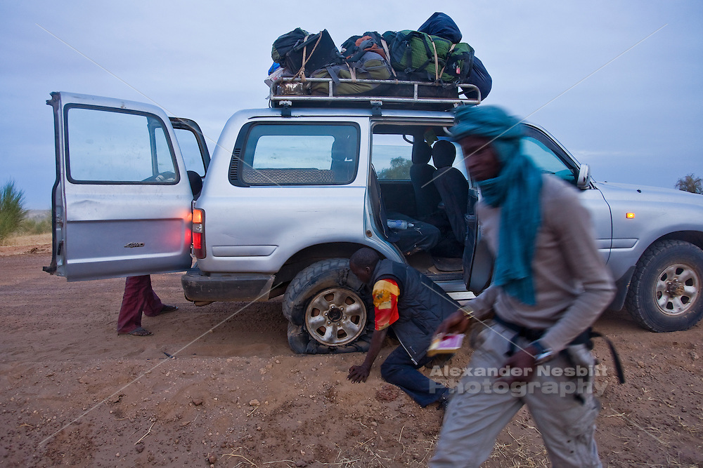 Mali, 2009 - The driver and two friends begin to deal with a mangled tire on a Land Cruiser  transporting travelers along the dirt track from Timbuktu to Douentza.