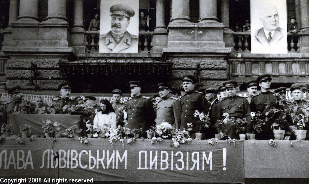 "General Nikita Khrushchev and Generals in Lvov, Ukraine during World War II with portrait of Stalin hanging from building.  From wikipedia, ""In the months following the German invasion, in 1941, Khrushchev, as a local party leader, coordinated the defense of Ukraine but was dismissed and recalled to Moscow after surrendering Kiev."""