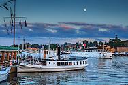 Fartyg en sen sommarkväll med månen vid restaurangen Ångbåtsbryggan vid Nybroviken Strandvägen i Stockholm