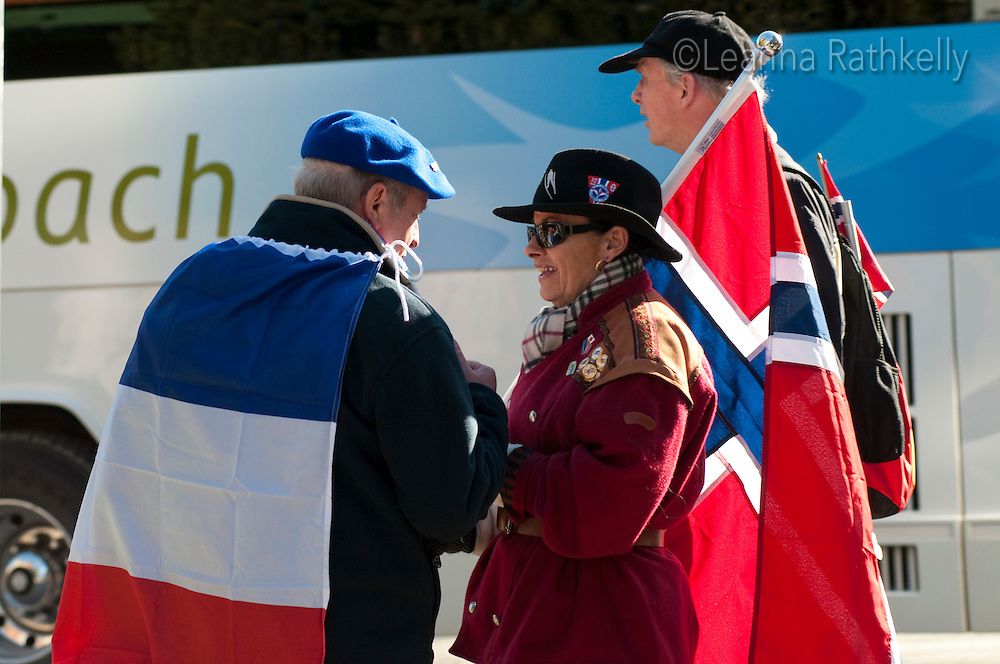 Two visitors, one wearing a flag from France and another carrying a Norwegian flag, stop for a friendly talk during the 2010 Olympic Winter Games in Whistler, BC Canada