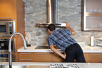 Back view of young man looking at chimney in model home kitchen