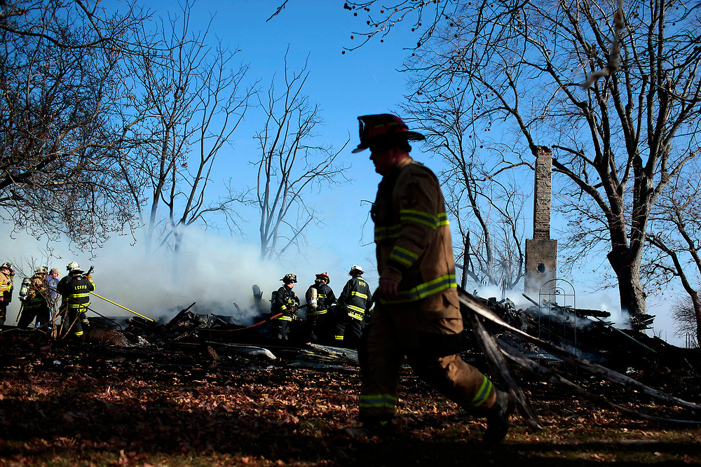 A firefighter pulls out a hose as crews work to extinguish a house fire on Turpin Road Friday, Nov. 19, 2010, in Decatur, Ill. Several area departments responded to the scene to keep the fire from spreading. (Herald & Review/ Stephen Haas)