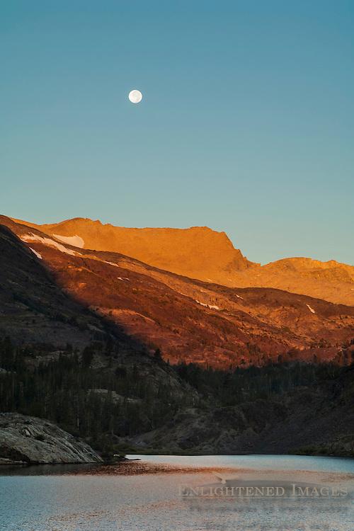 Full moon setting over mountains at sunrise over Ellery Lake; near Tioga Pass; Eastern Sierra; California
