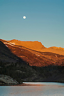 Full moon setting over mountains at sunrise over Ellery Lake; near Tioga Pass; Eastern Sierra; California
