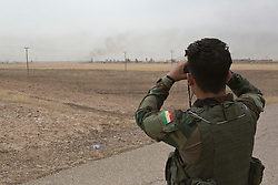 © Licensed to London News Pictures. 30/09/2015. Kirkuk, Iraq. A Kurdish peshmerga fighter surveys the village of Mansoria during an offensive aimed at capturing 11 villages from the Islamic State near Kirkuk, Iraq.<br /> <br /> Supported by large amounts of coalition airstrikes, members of the Iraqi-Kurdish peshmerga today (30/09/2015) took part in an offensive to take seven villages across a large front near Kirkuk, Iraq. By mid afternoon the Kurds had reached most of their objectives, but suffered around 10 casualties all to improvised explosive devices. All seven villages were originally Kurdish and settled with other ethnic groups during the Iraqi Arabisation process of the 1970's and 80's. Photo credit: Matt Cetti-Roberts/LNP
