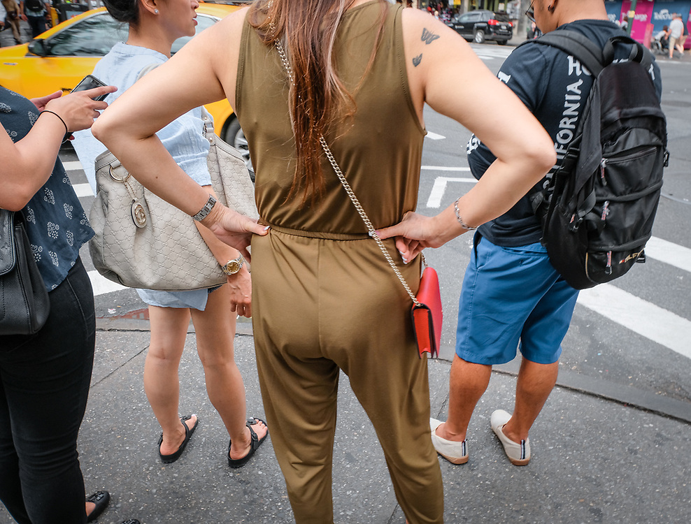 Woman with gold jumpsuit and tough stance on NYC street corner.
