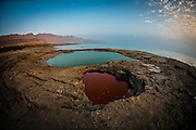 fisheye view of Water pools in sink holes on the shore of the Dead Sea, Israel