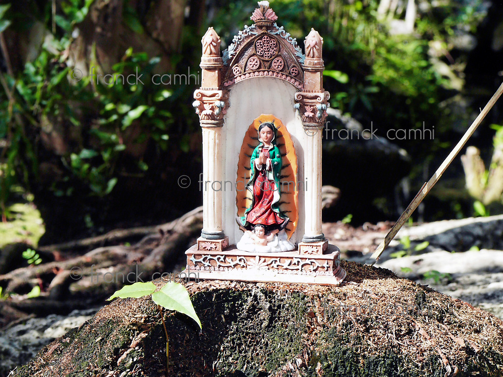 small mexican virgin mary altar posed on a rock in the yucatan jungle near a cenote entrance