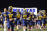 Milpitas High School junior, Eric Palomo (51), and the rest of the Trojans break through signage after halftime during the Oct. 5, 2012, home game against Mountain View.  Milpitas High School would go on to win 42-7.  Photo by Stan Olszewski/SOSKIphoto.