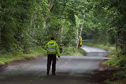 © Licensed to London News Pictures . 01/08/2015 . Cheshire , UK . A police officer walking down a closed Coach Road , along which the plane has crashed . Scene in Oulton Park , Cheshire , where a plane has crashed and one person has died this afternoon (1st August 2015) during the Carfest2015 event . Photo credit : Joel Goodman/LNP