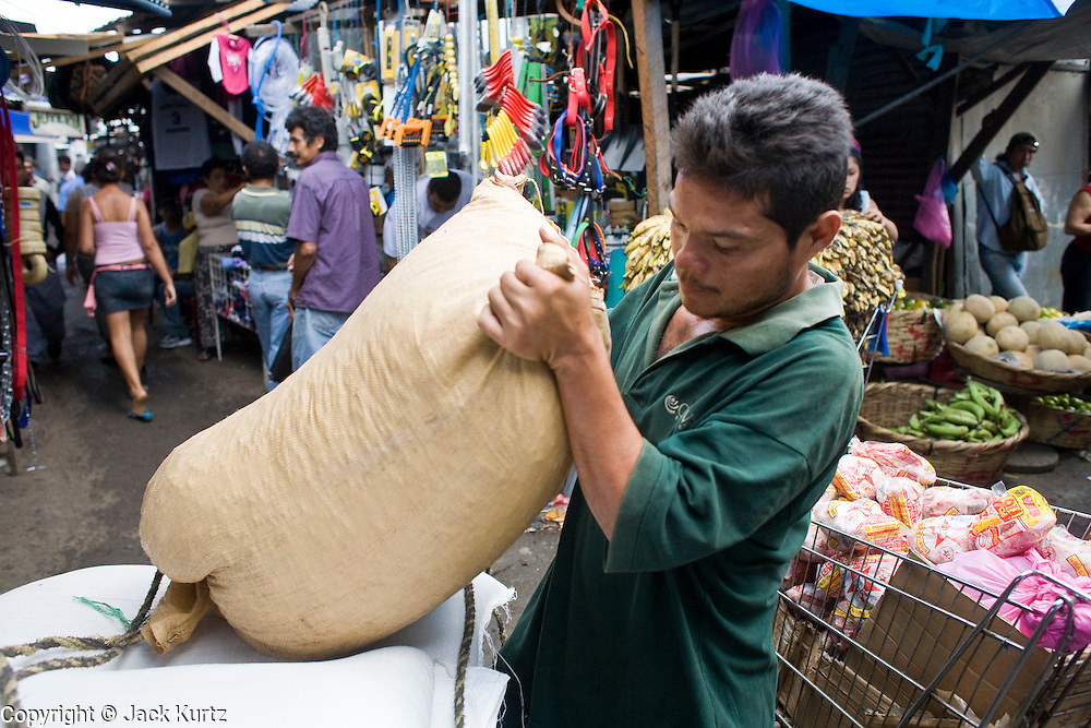 08 JANUARY 2007 - MANAGUA, NICARAGUA: A man loads a bag of rice onto a hand cart in Mercado Oriental, the main market that serves Managua, Nicaragua. The market encompasses dozens of square blocks and is the largest market in Central America.    PHOTO BY JACK KURTZ