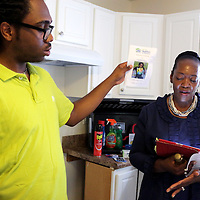 Homeowner Christian Pierce uses a program to fan Pastor Janice Harris Sunday June 22, 2014 during a Cape Fear Habitat for Humanity dedication ceremony of a recently completed home on Tiffany Drive in Wilmington, N.C. (Jason A. Frizzelle)