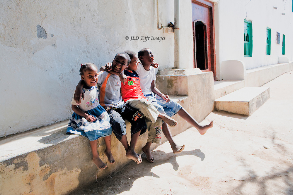 Oman, in the village of Mirbat.  Four laughing children seated together on a bench outside one of the village houses. Their bare feet swing merrily in the sunshine.