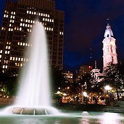 The fountain of Fairmount Park with the City Hall tower in the background at night.