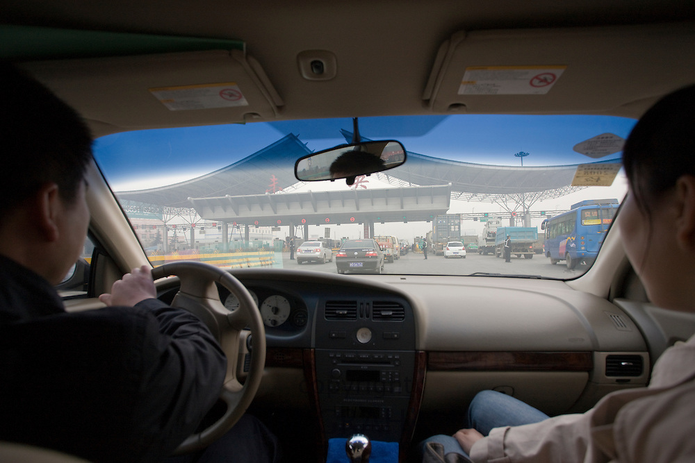 Chinese driver and passenger in car approaching motorway toll, Xian, China