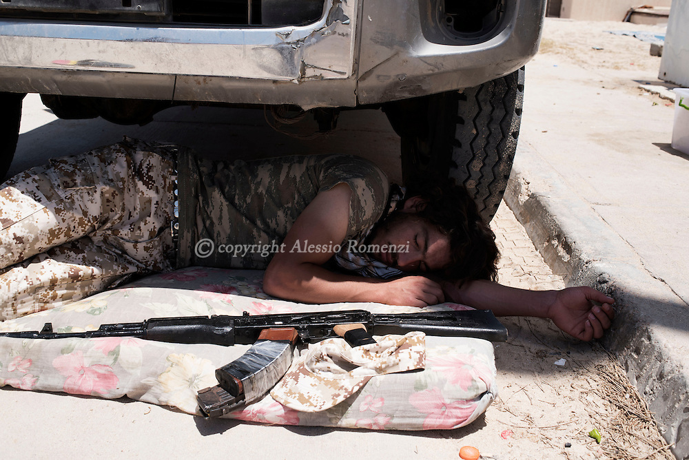 Libya: A Libya's Government of National Accord's (GNA) fighter sleeps under the shadow of a military car on the western frontline with ISIS in Sirte, Alessio Romenzi