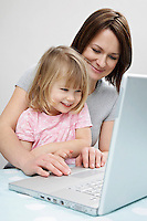 Girl (3-4) sitting on mother's lap looking at laptop smiling
