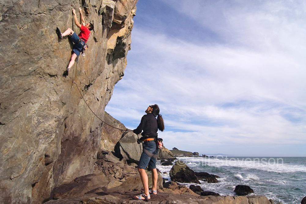 A picture of a man rock climbing next to the ocean at Mickey's Beach in California
