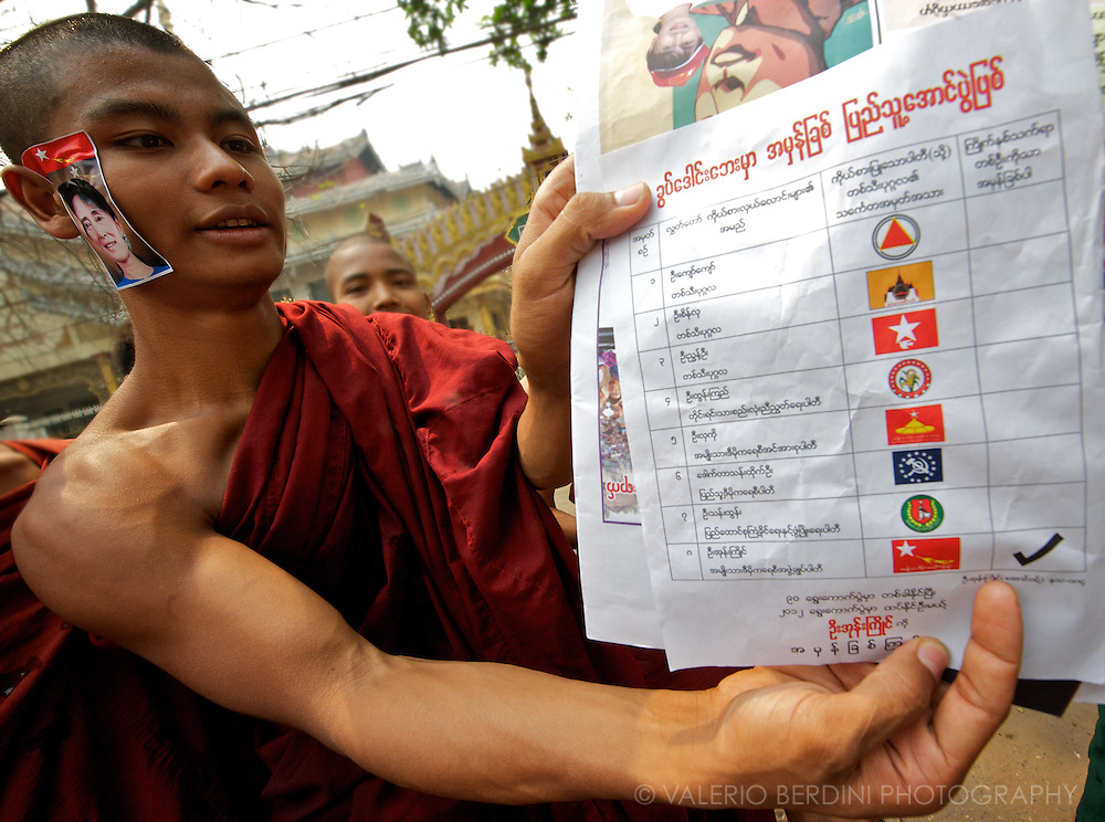 A monk displays a copy of the ballot paper ticked at the symbol of the NLD.