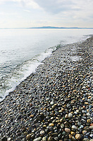Small waves breaking on the stones that make the beach on Lincoln Park in West Seattle on the Puget Sound.