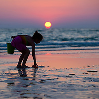 Children collect shells as the sun sets at St. Pete Beach.