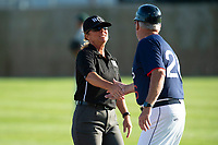 KELOWNA, BC - JULY 24: the Kelowna Falcons' assistant coach shakes hands with the umpire against the Yakima Valley Pippins at Elks Stadium on July 24, 2019 in Kelowna, Canada. (Photo by Marissa Baecker/Shoot the Breeze)